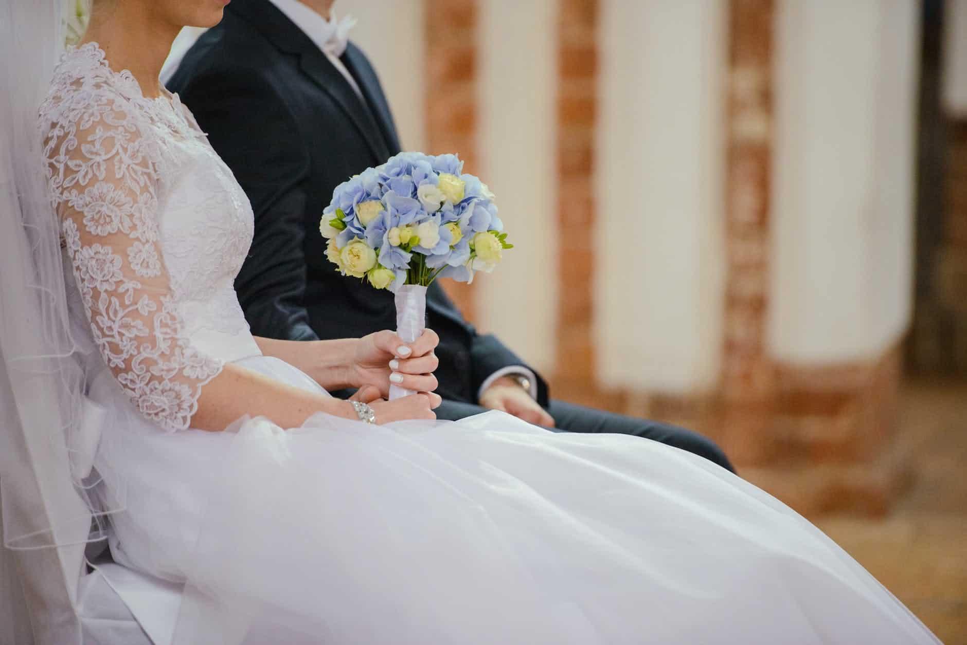 unrecognizable young newlyweds sitting together during wedding celebration