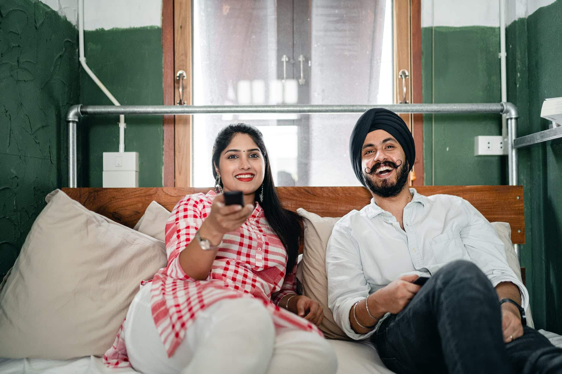 happy young indian couple watching tv in bedroom together