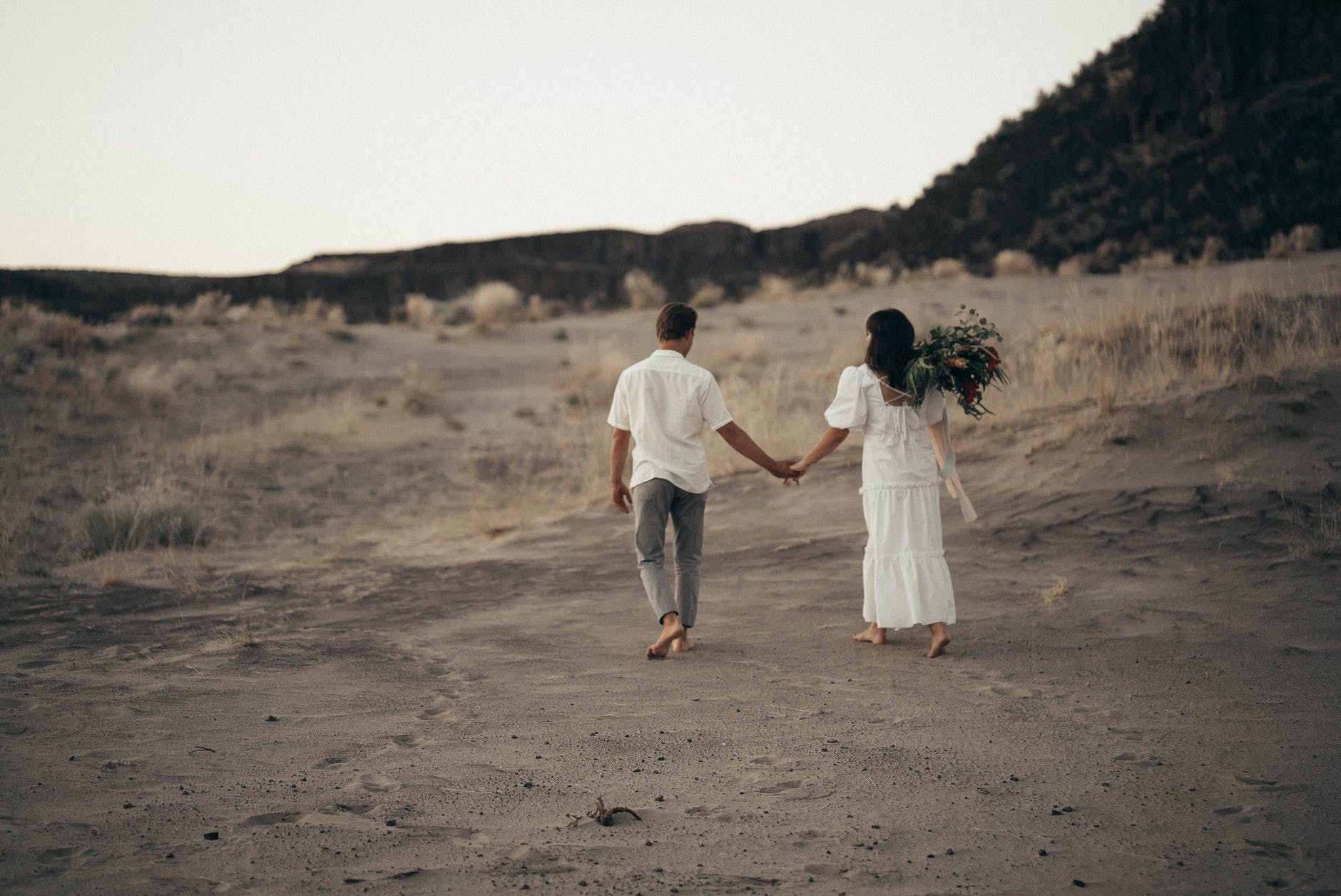 unrecognizable wedding barefoot couple walking on sandy terrain