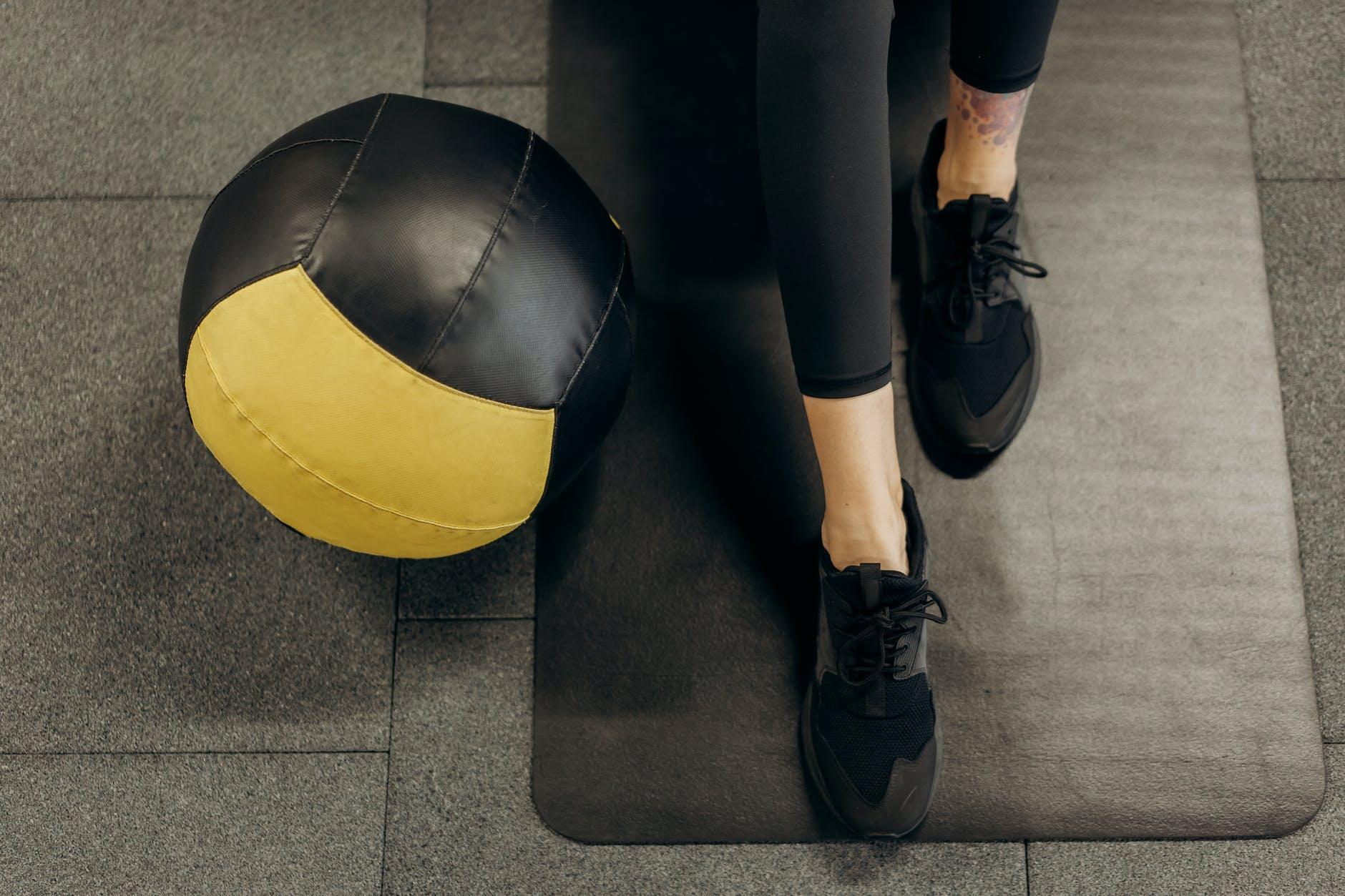 person standing on a mat beside a ball