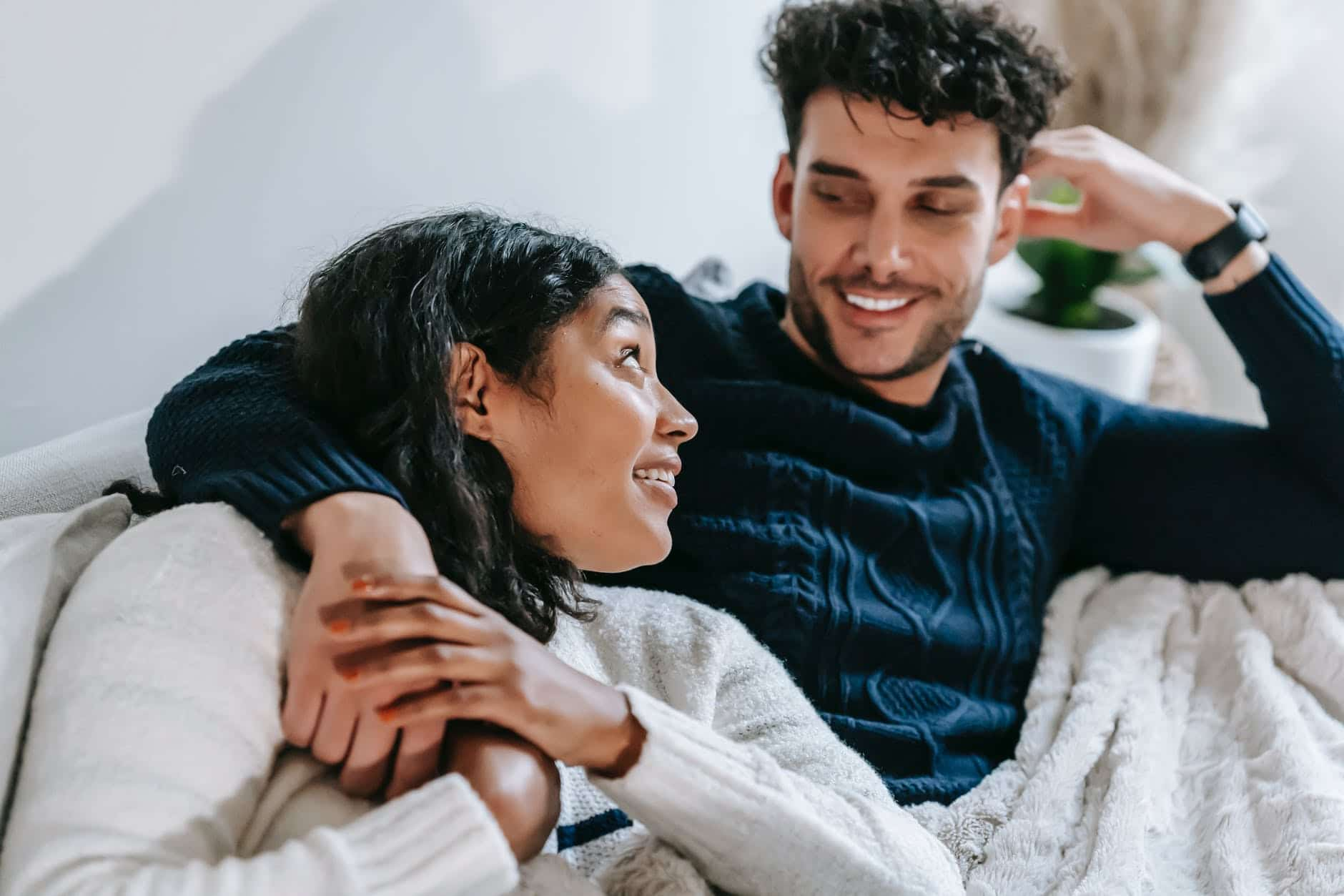 cheerful multiethnic couple resting on couch under blanket
