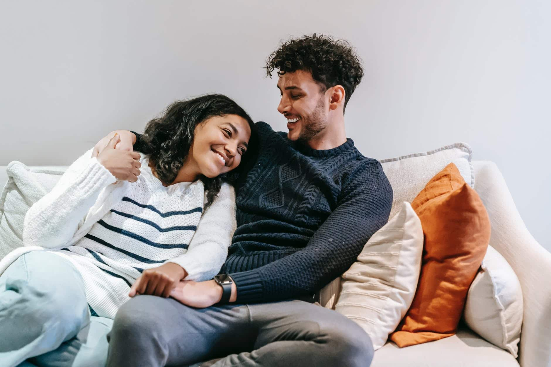 smiling multiracial couple hugging on couch