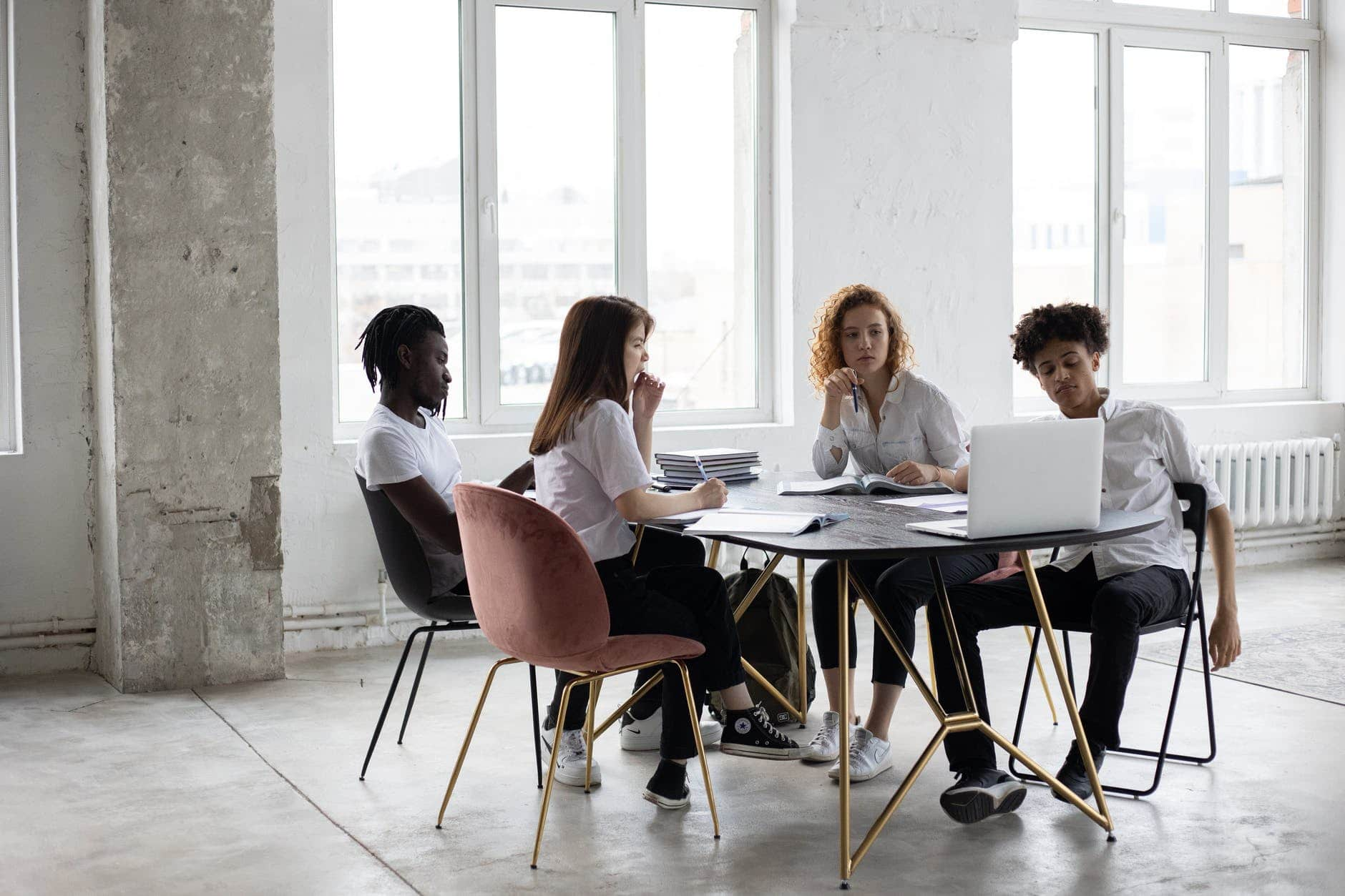 focused diverse colleagues analyzing project together in office
